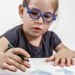 Cute Little Girl with Blue Glasses Painting on a School Desk — Стоковое фото