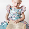Cute Little Girl Reading an Old Red Book — Stock Photo #36375413