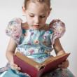 Cute Little Girl Reading an Old Red Book — Stock Photo #36375419