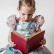 Cute Little Girl Reading an Old Red Book — Stock Photo