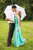 Kissing under umbrella — Stock Photo