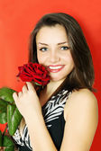 Woman with rose on a red — Stock Photo