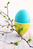 Turquoise egg in yellow stand — Stock Photo