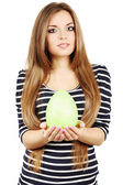 Woman holds a green egg — Stock Photo