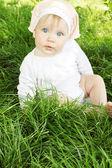 女の子は草の上に座っています。 — ストック写真