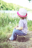 Girl sitting on the bank of the river — Stock Photo