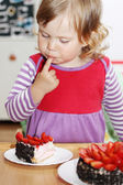Girl eating cake with strawberries — Stock Photo