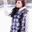 Girl in a fur vest catches snow — Stock Photo #34251491