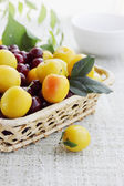 Yellow plums in a basket — Stock Photo