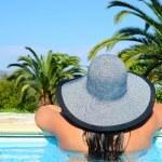 Portrait of woman enjoying sun in swimming pool — Stock Photo