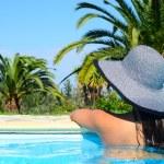 Beautiful woman enjoying sun at swimming pool — Stock Photo