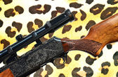 Hunting concept - Rifle gun and leopard fur texture — Stock Photo