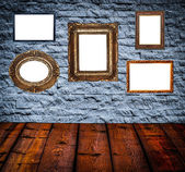 Retro room with antique picture frames on stone wall — Stock Photo