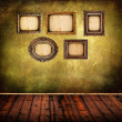 Old room with grunge wall and vintage frames — Stock Photo