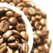 Coffee cup filled with coffee beans — Stock Photo