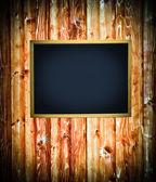 Empty board on wooden wall — Stock Photo