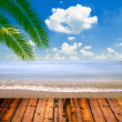 Photo: Tropical seand beach with palm leaves and wooden floor