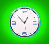 Retro blue clock on green background — Stock Photo