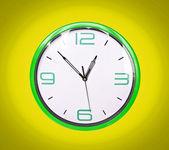 Retro green clock on yellow background — Stock Photo