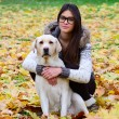 Stock Photo: Beautiful girl with labrador retriever in Autumn forest