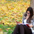 Beautiful brunette girl reading book in nature — Stock Photo