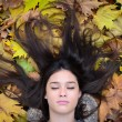 Stock Photo: Portrait of beautiful brunette woman lying on maple leaves