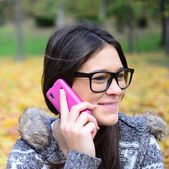 Beautiful smiling student girl talking on cell phone — Stock Photo