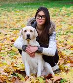 Vacker flicka med labrador retriever i höst skog — Stockfoto