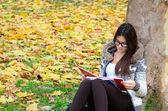 Piękna brunetka dziewczynka czytania książki w przyrodzie — Zdjęcie stockowe