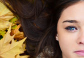 Woman face lying on autumn leaves — Stock Photo