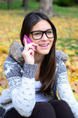 Young beautiful smiling woman talking on cell phone — Stock Photo
