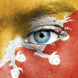 Human face painted with flag of Bhutan — Stock Photo