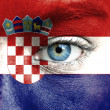 Human face painted with flag of Croatia - Stock Photo