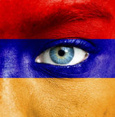 Human face painted with flag of Armenia — Stock Photo