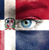 Human face painted with flag of Dominican Republic — Stock Photo