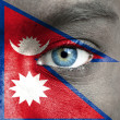 Human face painted with flag of Nepal — Stock Photo