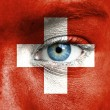 Human face painted with flag of Switzerland — Stock Photo