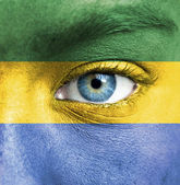 Human face painted with flag of Gabon — Stock Photo