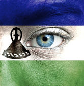 Human face painted with flag of Lesotho — Stock Photo