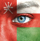 Human face painted with flag of Oman — Stock Photo