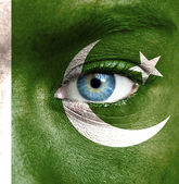 Human face painted with flag of Pakistan — Stock Photo