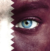 Human face painted with flag of Qatar — Stock Photo