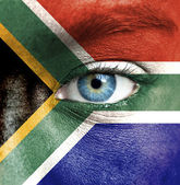 Human face painted with flag of South Africa — Stock Photo