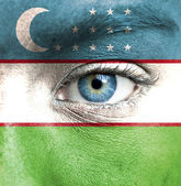 Human face painted with flag of Uzbekistan — Stock Photo