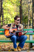 Man playing guitar on bench in park — Photo