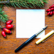 Blank paper note with pen and Christmas tree branches on wooden - Stock Photo