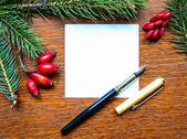 Nota di carta bianca con rami di albero di natale e penna su legno — Foto Stock