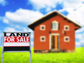 """LAND FOR SALE"" sign against wooden house - Real estate concept — Stock Photo"