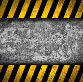 Grunge metal background with black and yellow warning stripes — Stock Photo