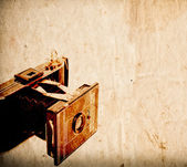 Antique camera on vintage paper background — Stock Photo